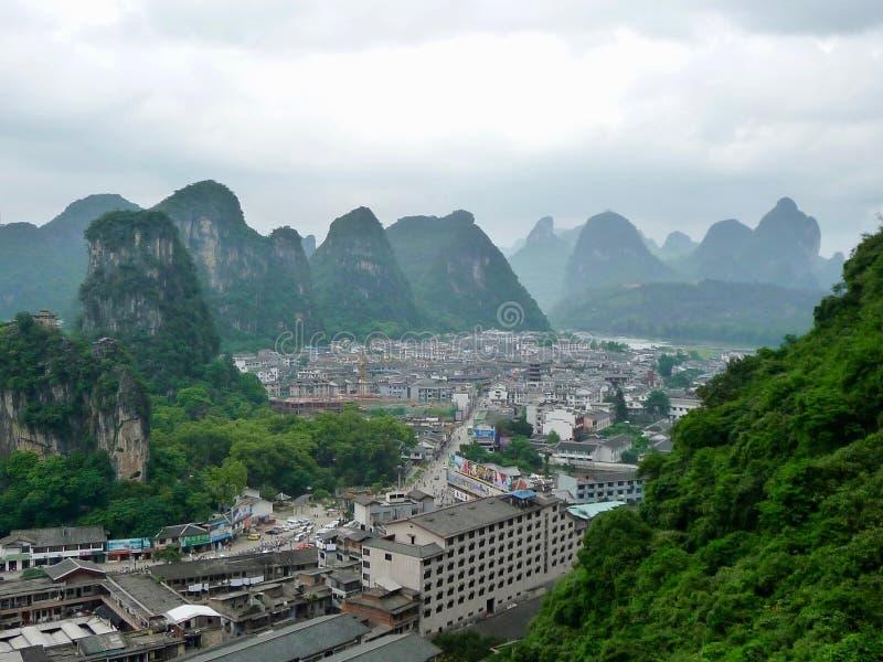 Staden av Yangshuo, Kina med staden som kura ihop sig i karstberg i misten och molnen royaltyfria foton