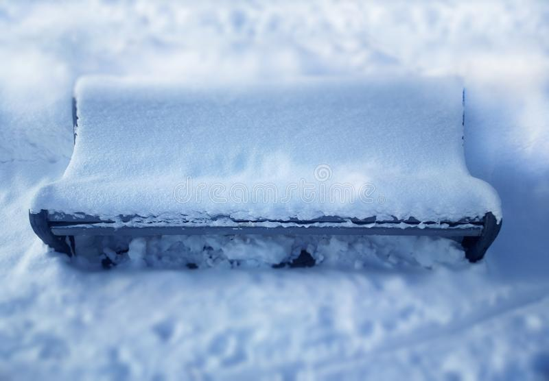 Staden parkerar bänken som täckas med snöbakgrund arkivfoton