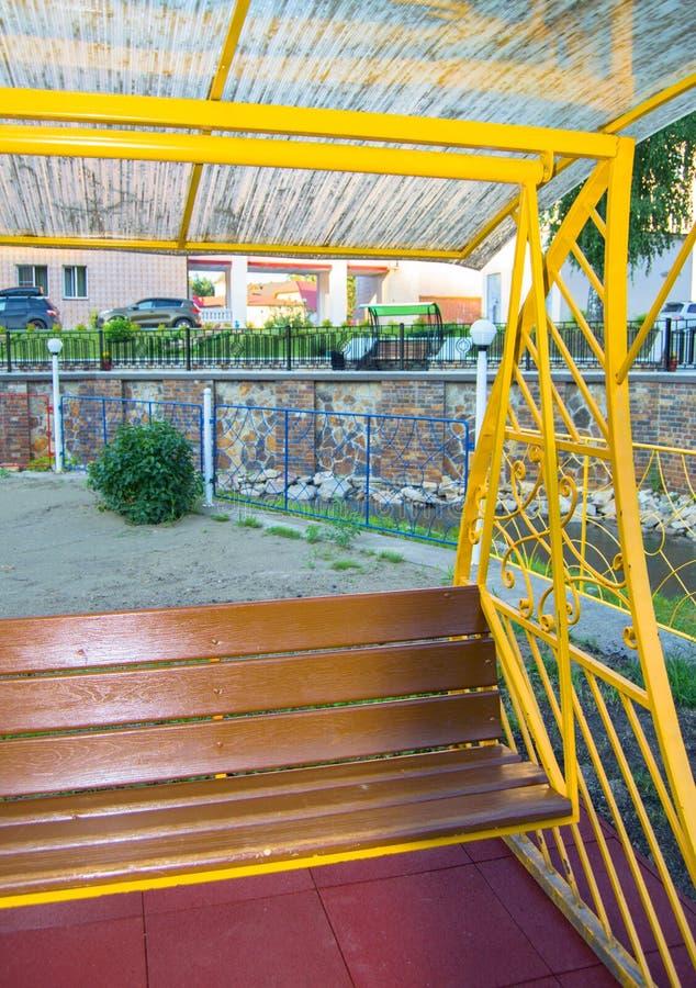 Staden parkerar i sommar, tom trägunga med den gula dekorativa metallramen, utomhus- fritidmöblemang, vertikal ram fotografering för bildbyråer