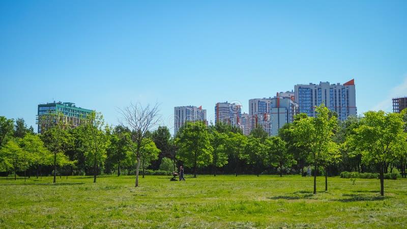 Staden parkerar under blå himmel med i stadens centrum horisont i bakgrunden arkivfoton