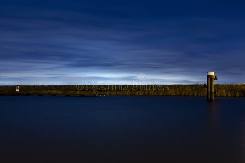 Staden skylight bakom en dyke i hamnen i Bruinisse royaltyfria foton