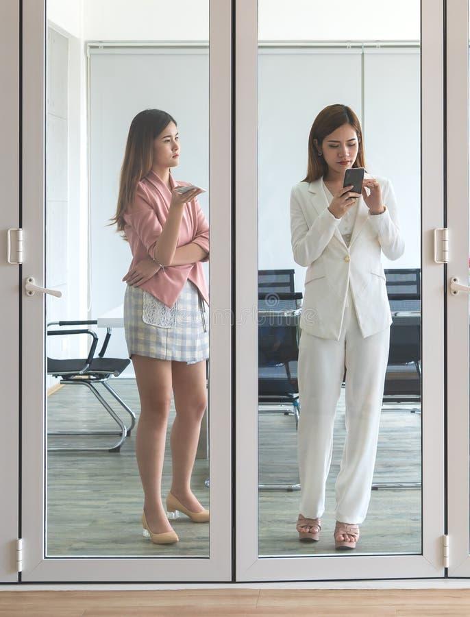stading在meetin屋子窗口里的女商人队 库存照片