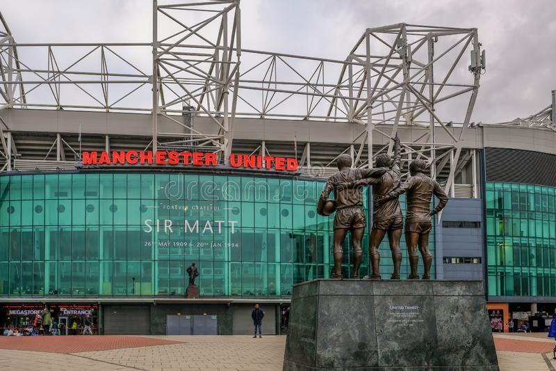 Stadio di football americano di Manchester United con la statua di meglio, di legge e di Charlton nella priorità alta fotografia stock libera da diritti