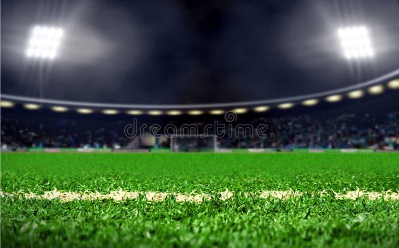 Stadion för fotbollfält med grönt gräs och ljusa strålkastare på natten arkivbilder