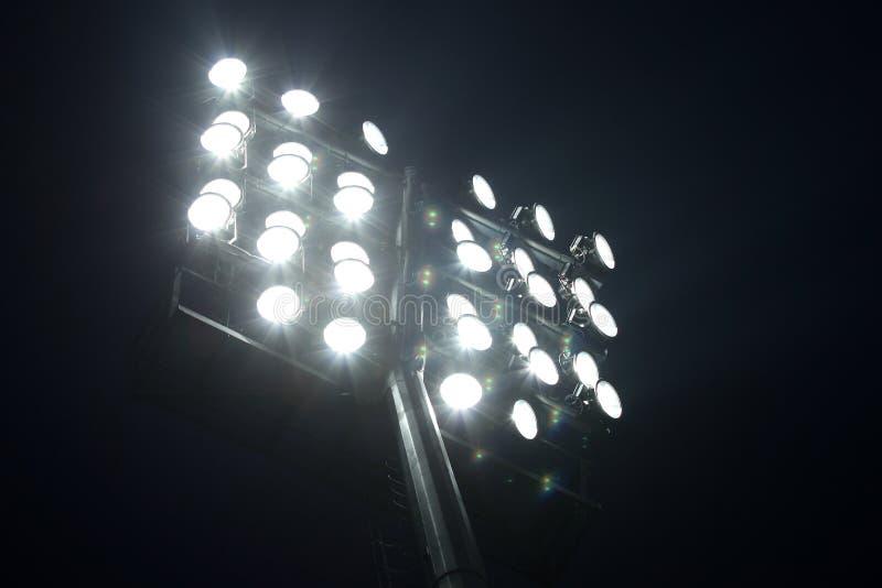 Stadionfotbollljus över mörk bakgrund för natthimmel royaltyfri foto