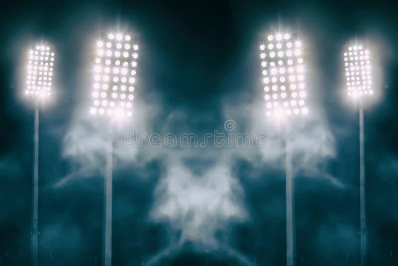 Stadionslichter und -rauch gegen dunklen nächtlichen Himmel stockfotografie