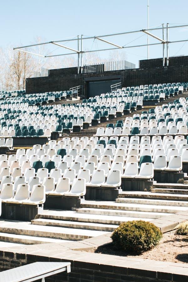 Stadiontribunes met doorgangen en witte en grijze plastic zetels royalty-vrije stock foto