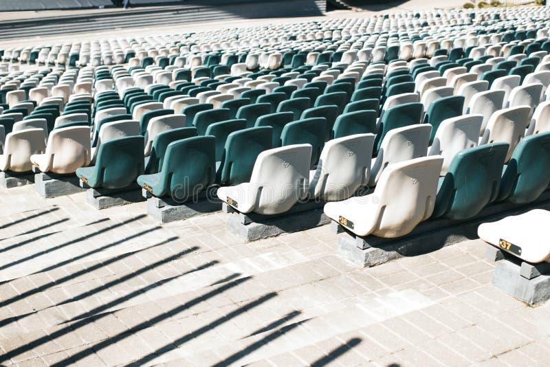 Stadiontribunes met doorgangen en witte en grijze plastic zetels stock afbeelding