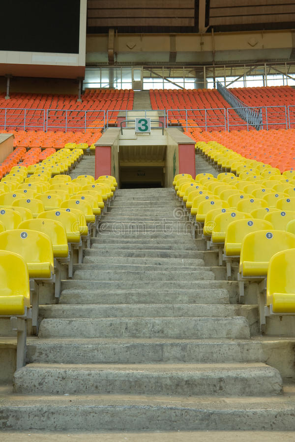 Stadium. Rows of yellow, red and orange seats on the stadium with fences around the edges of the sectors stock photography