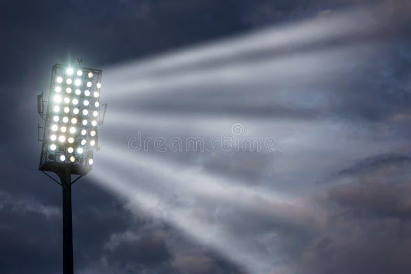 Stadium lights against dark night sky stock image