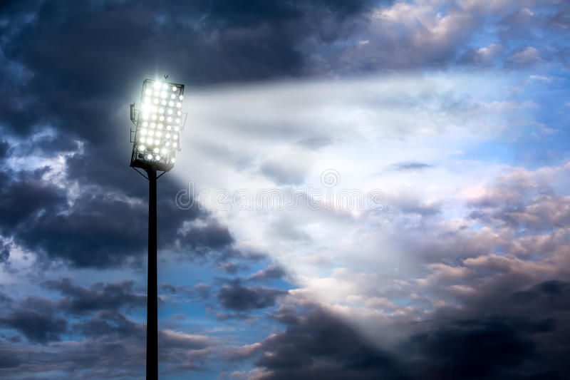 Stadium lights against dark night sky stock photo