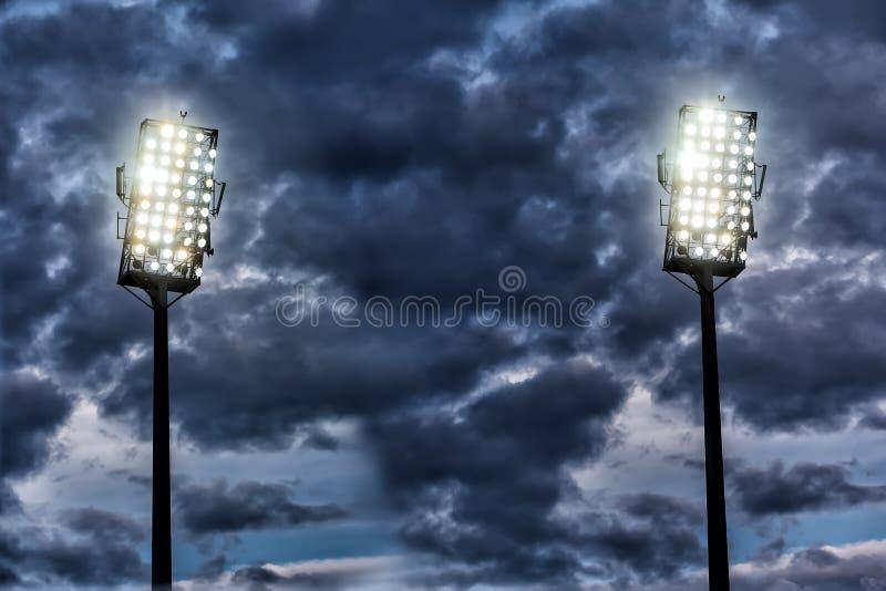 Stadium lights against dark night sky stock photos