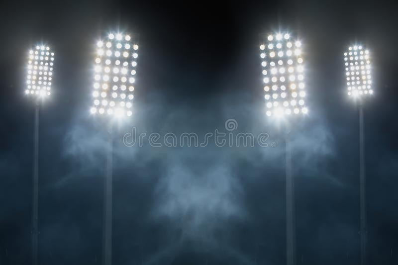 Stadium lights and smoke against dark night sky stock photography