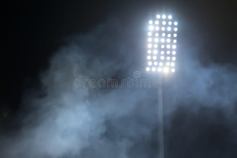 Stadium lights and smoke against dark night sky royalty free stock photo