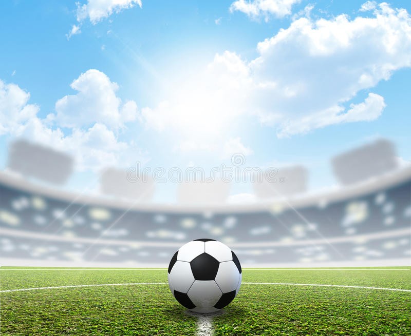 Stadium Soccer Pitch And Ball. A soccer stadium with a marked green grass pitch and a soccer ball in the center in the daytime under a blue sky stock images