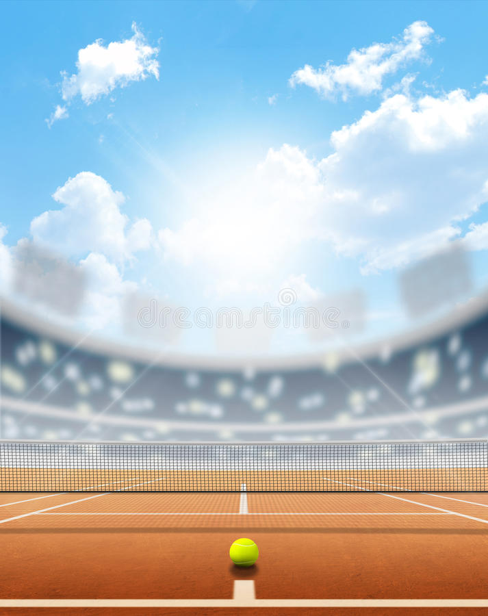 Stadium And Tennis Court. A tennis court in an arena with a marked clay surface in the daytime under a blue sky stock image