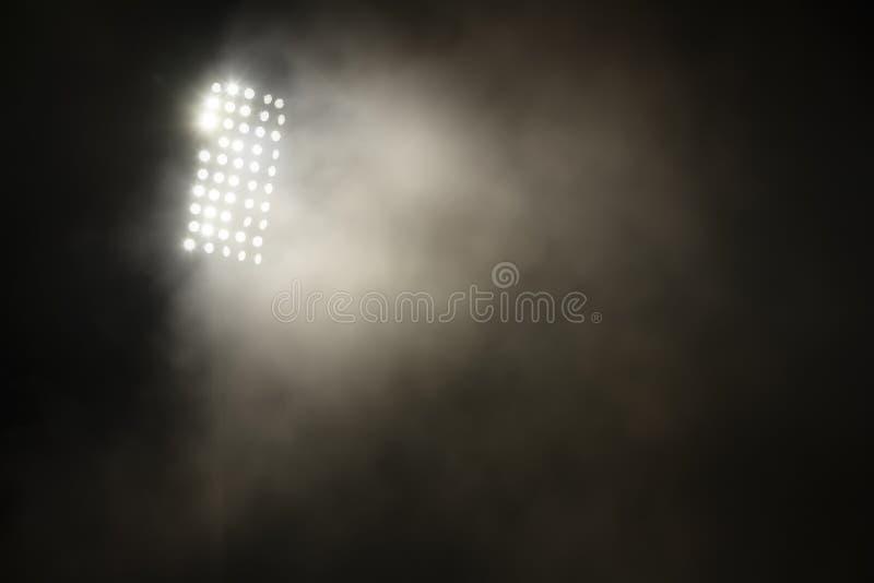 Stadiumlichten en rook tegen donkere nachtelijke achtergrond stock foto's