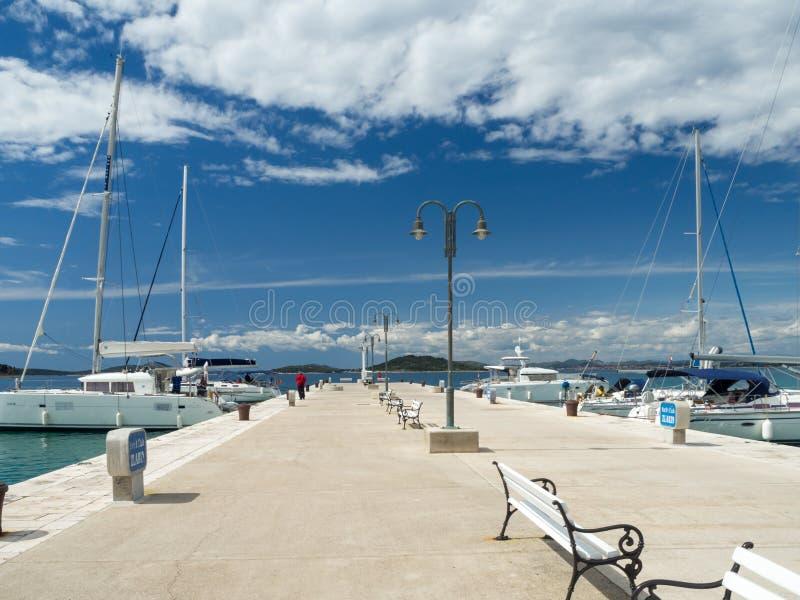Stadpir i den Zlarin ön i Kroatien, portflotta med yachter och katamaran royaltyfri foto