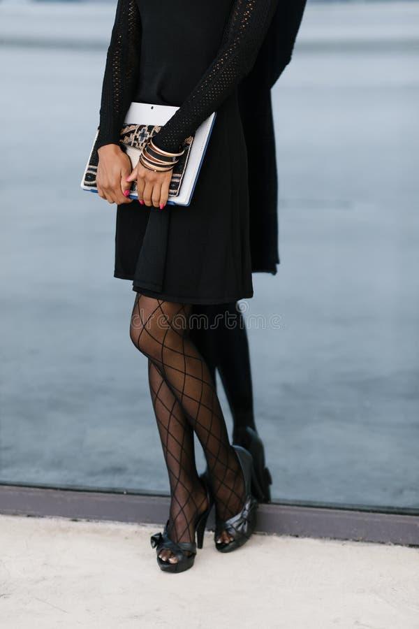 Stads- affärskvinna utanför att rymma handväskan och minnestavlan royaltyfri fotografi