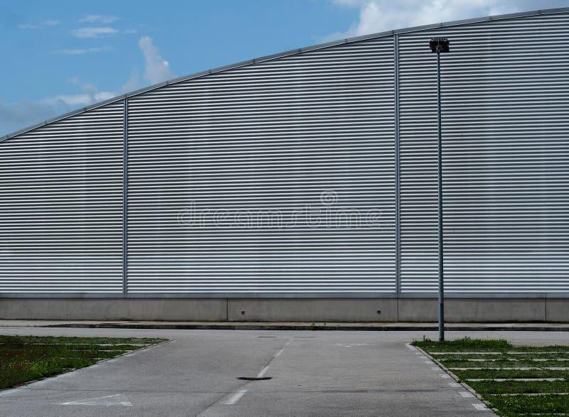 Stads- bakgrund f?r kopieringsutrymme Tom väg som är främst av en modern byggnad för aluminiumcladding, med halvcirkelformig form royaltyfri fotografi