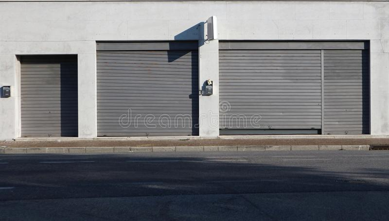 stads- bakgrund Shoppa detaljhandel med metallslutare som stängs på trottoaren på sidan av vägen royaltyfri fotografi
