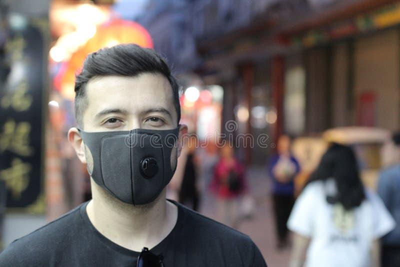 Stads- bild av den unga mannen med föroreningmaskeringen arkivfoton