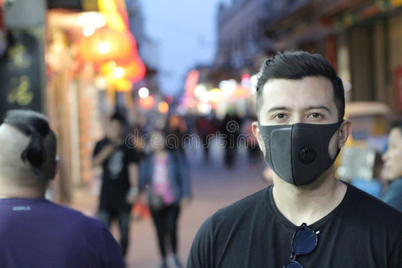 Stads- bild av den unga mannen med föroreningmaskeringen royaltyfri fotografi