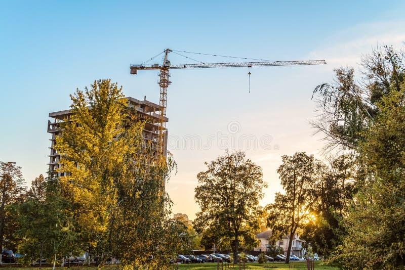 Stads- bostadsbyggande Tornkran med envåning byggnad under konstruktion i aftonen bland höstträd royaltyfri foto