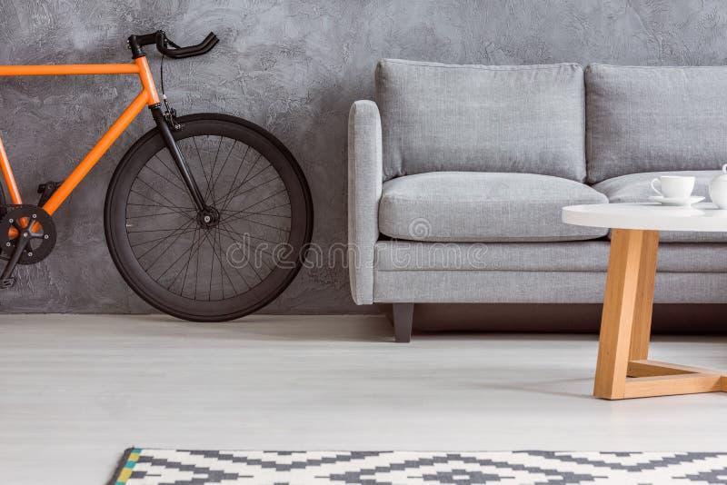 Stads- cykel och grå färgsoffa royaltyfri foto