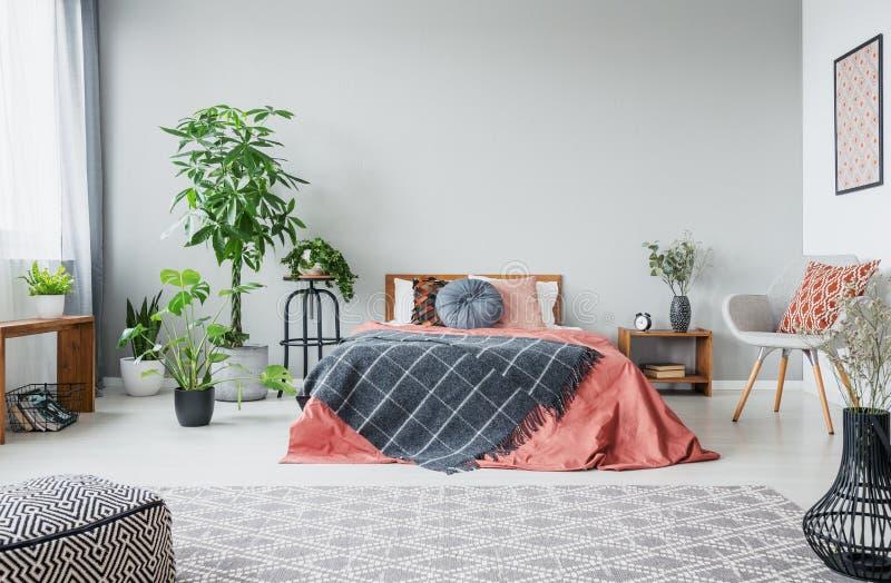 Stads- djungel i modernt sovrum med konungformatsäng, den bekväma gråa fåtöljen och mönstrad matta arkivfoto