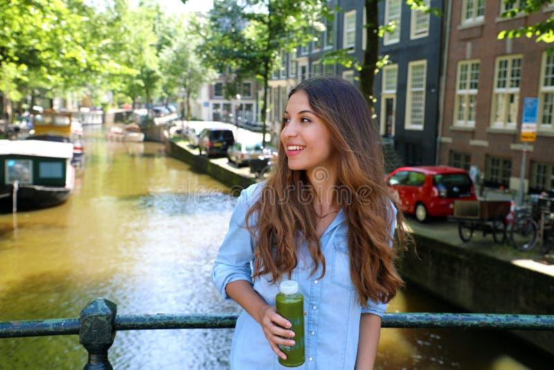 Stads- drinkar för flicka för stadslivsstilhipster gör grön fruktsaft på den Amsterdam kanalen, Nederländerna Den sunda detoxstri royaltyfria bilder