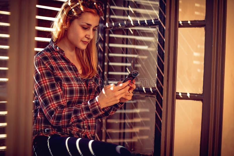 Stads- flicka som rymmer en mobiltelefon och smsar messaging arkivbilder