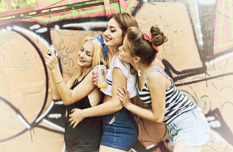 Stads- flickor har gyckel med väggen för grunge för den retro tappningfotokameran den utomhus- near, den tonade bilden royaltyfri foto