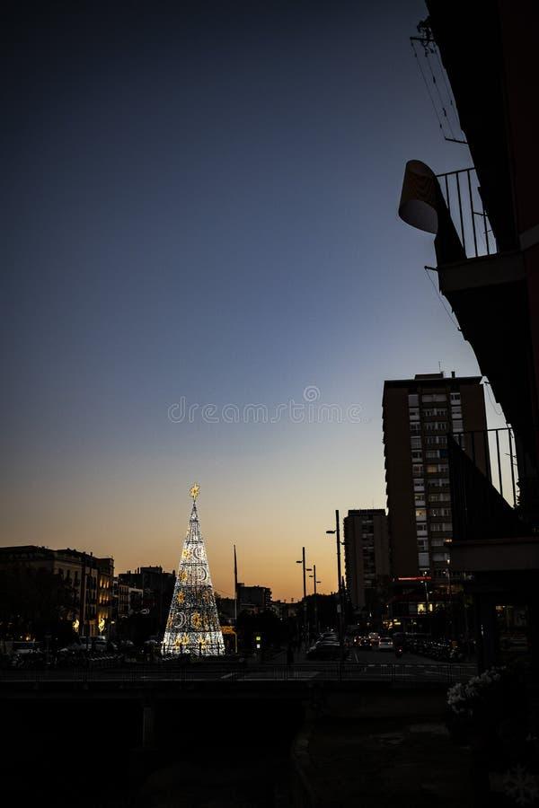 Stads- garneringljus för jul på en svart konturhorisont royaltyfri bild
