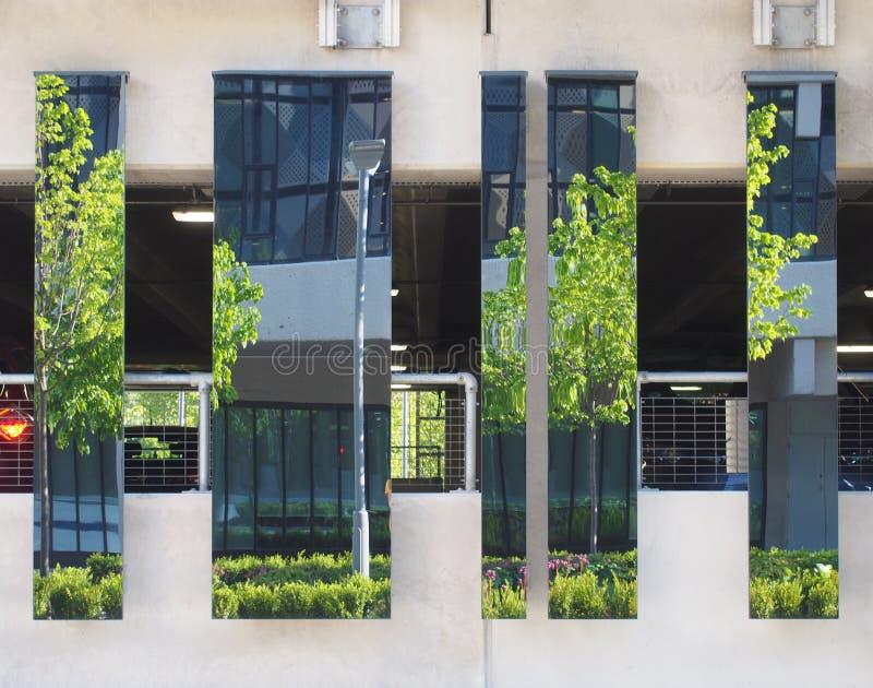 Stads- gataplats med modern kontorsbyggnad och träd reflekterade i spegelförsedda yttersidor på en parkeringshusstruktur arkivbilder
