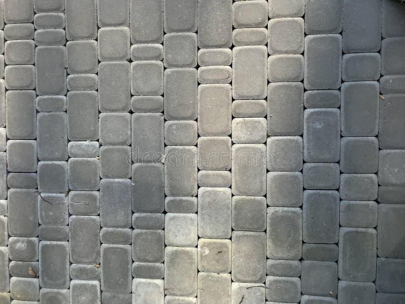 Stads- gr? bakgrund f?r grov grunge av stenl?gga tjock skiva f?r stenfyrkant fotografering för bildbyråer