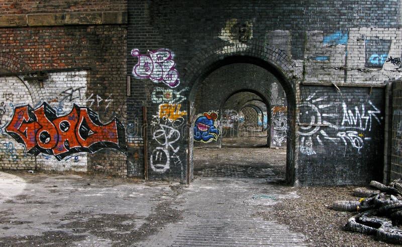 Stads- grafitti på en Manchester rad av bågar arkivfoto