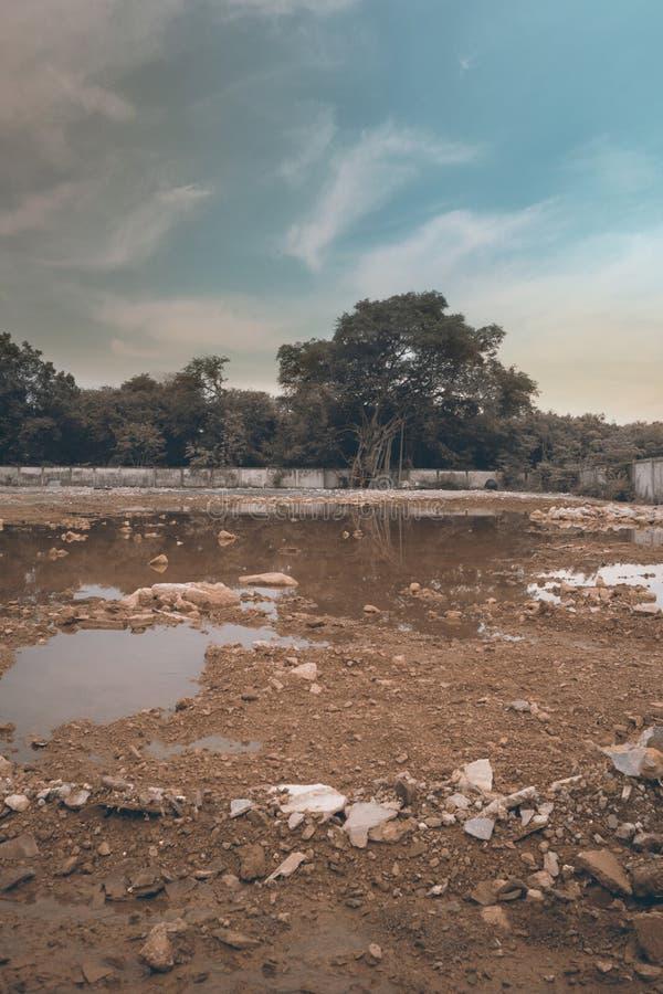 Stads- område för rivningkonstruktionsplats med avfallsbetongstenen och det smutsiga dammet i solnedgångtiden med blå himmel för  royaltyfria foton