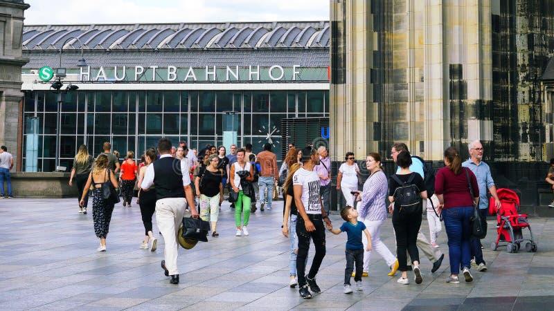 Stads- pendlare, turisten och shoppare i dagstidning rusar utanför den berömda huvudsakliga drevstationen i Cologne, Tyskland arkivfoto