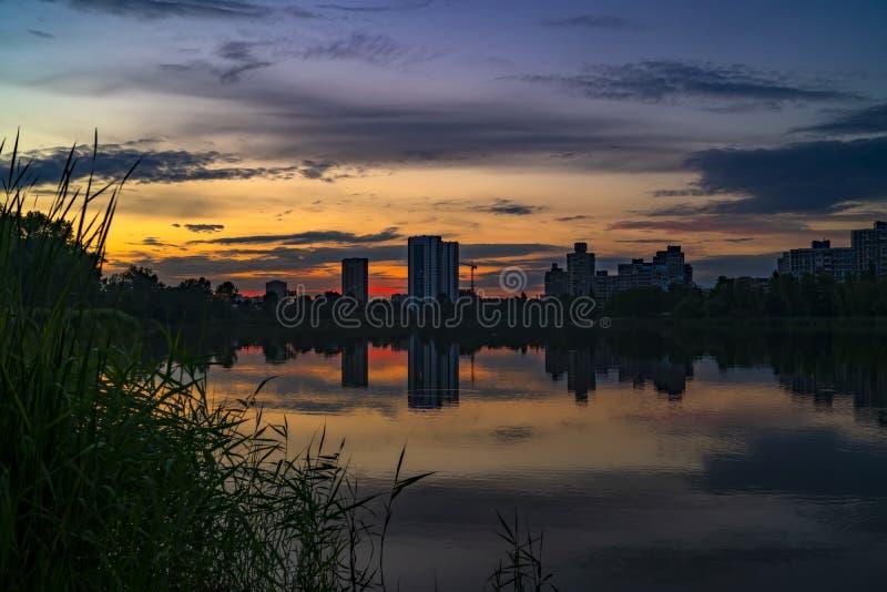 Stads- solnedgång med konturer av stadsbyggnader på färgrik himmel- och sjöbakgrund royaltyfria foton