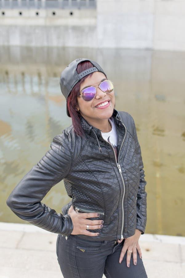 Stads- stående av att le den latinska kvinnan för mode med solglasögon och baseballmössan royaltyfri bild
