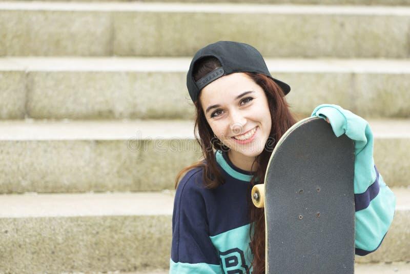 Stads- stående av den gladlynta unga kvinnan med skateboarden fotografering för bildbyråer