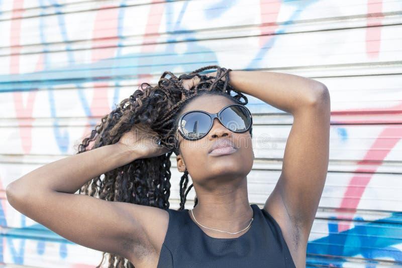 Stads- stående av den härliga afrikanska kvinnan med solglasögon, hår royaltyfri foto