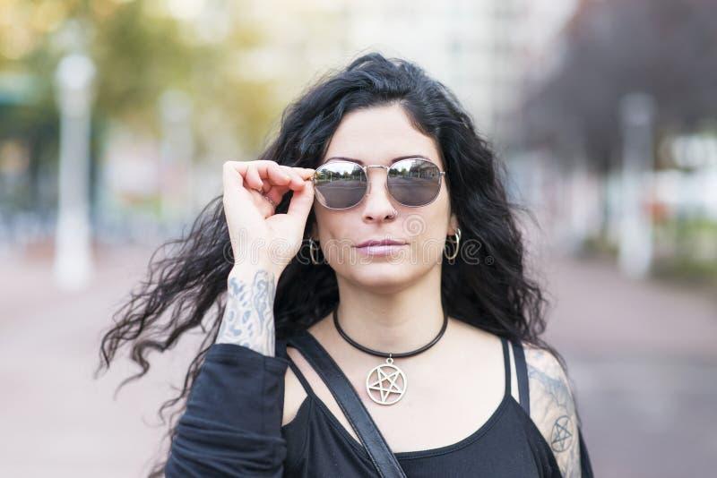 Stads- stående av den härliga kvinnan med solglasögonheavy metalst royaltyfri foto