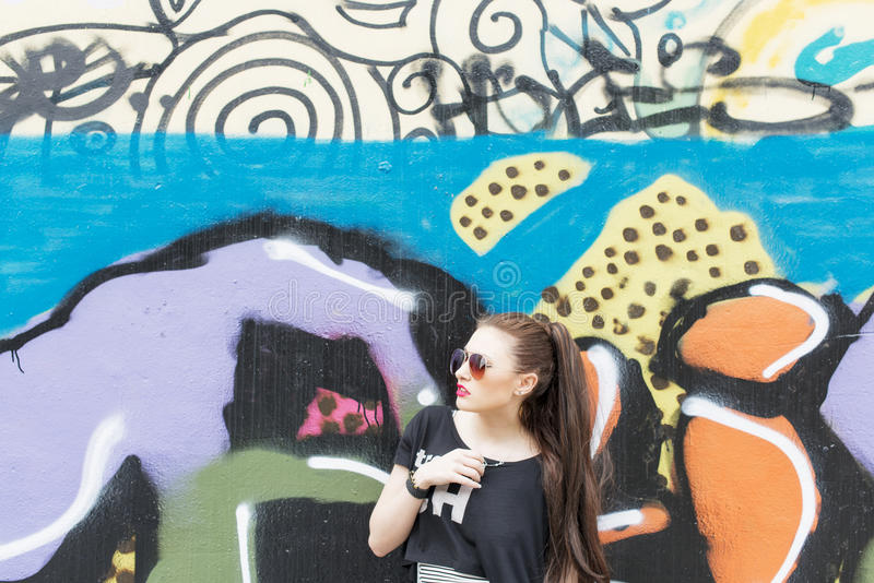 Stads- stående av den härliga unga kvinnan på grafittibakgrund arkivfoto