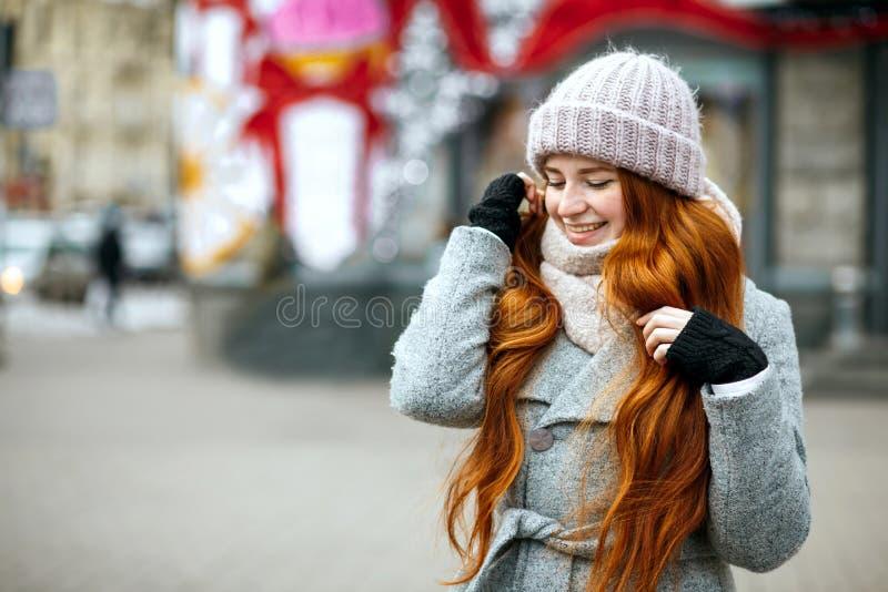 Stads- stående av den nöjda ljust rödbrun flickan med bärande krig för långt hår royaltyfria bilder
