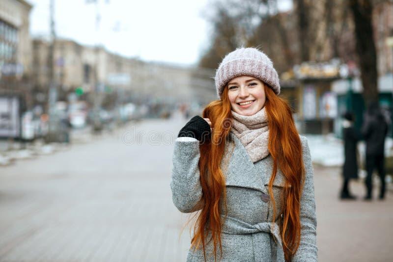 Stads- stående av den positiva ljust rödbrun kvinnan med långt hår som bär w arkivfoton