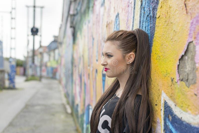 Stads- stående av den unga kvinnan i gatan med grafitti royaltyfri bild