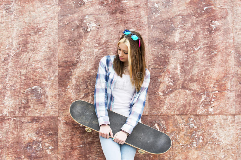 Stads- stående av härligt med skateboarden som bort ser royaltyfri bild