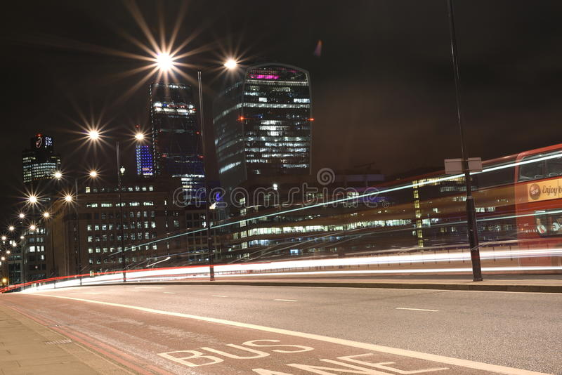 Stads- stadsnattskott på den London bron, röd buss i rörelse, långt exponeringsskott fotografering för bildbyråer